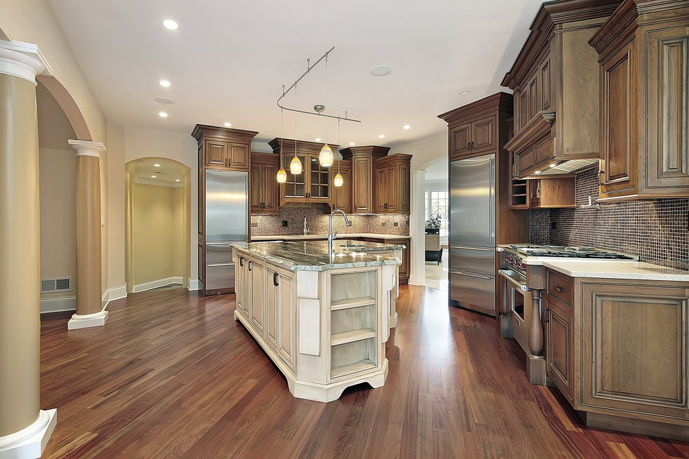 This kitchen features hardwood flooring and a center island with a stylish countertop lighted by pendant lights.