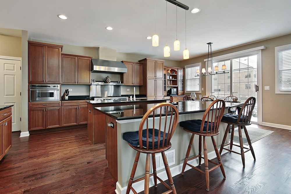 Wooden counter stools with blue cushions sit at a black marble top kitchen island illuminated by four glass pendant lights. Kitchen wood cabinet surrounds a stainless steel range hood.