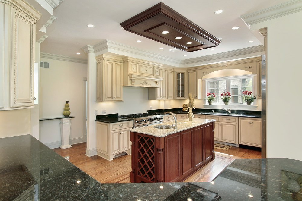 A small kitchen featuring black granite countertops on the kitchen counters and a marble countertop on the center island.