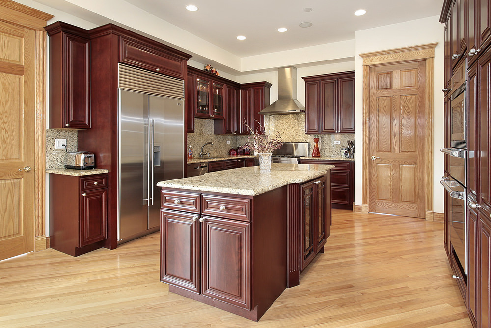 A gorgeous redwood cabinet surrounds the stainless steel fridge and marble backsplash on this elegant kitchen. It has recessed lighting and breakfast island with a marble countertop that matches the backsplash.