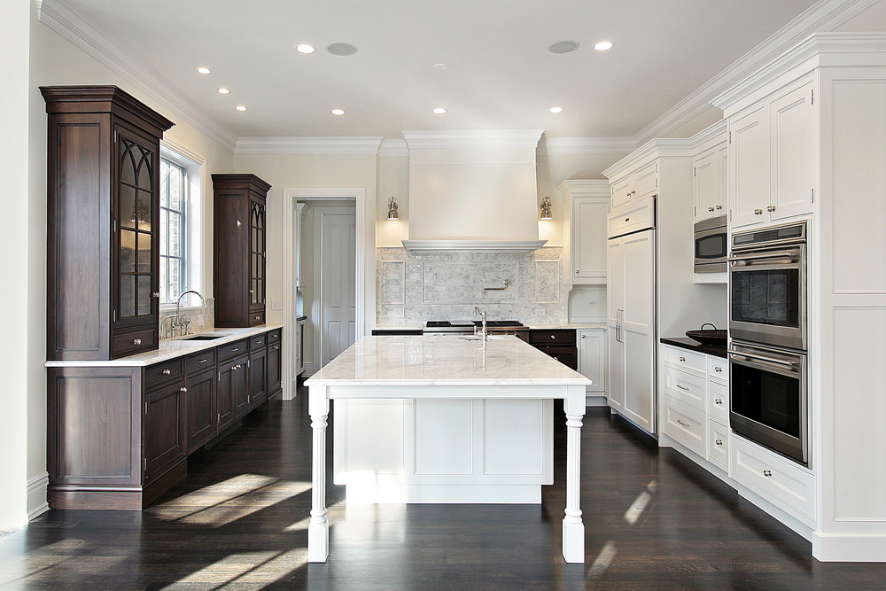A sleek kitchen features contrasting white and dark wood cabinets over the hardwood flooring. Between them is a white center kitchen island with marble countertop against the covered range hood.