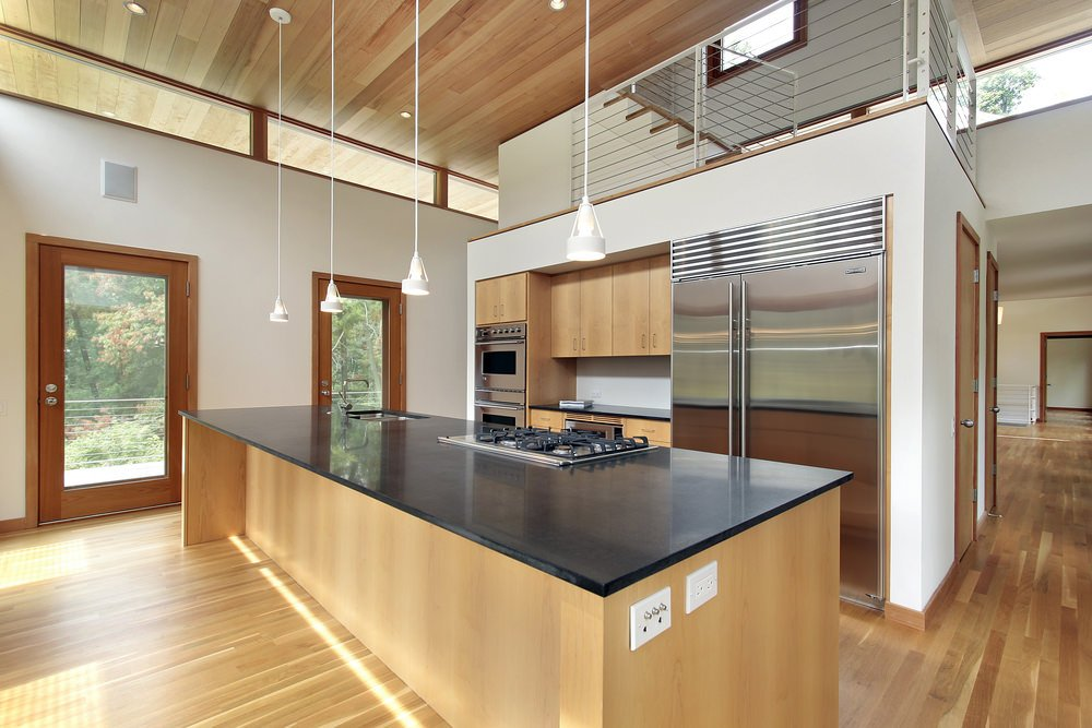 This industrial kitchen boasts hardwood flooring matching the high ceiling with pendant lights. The center island features smooth black countertop.