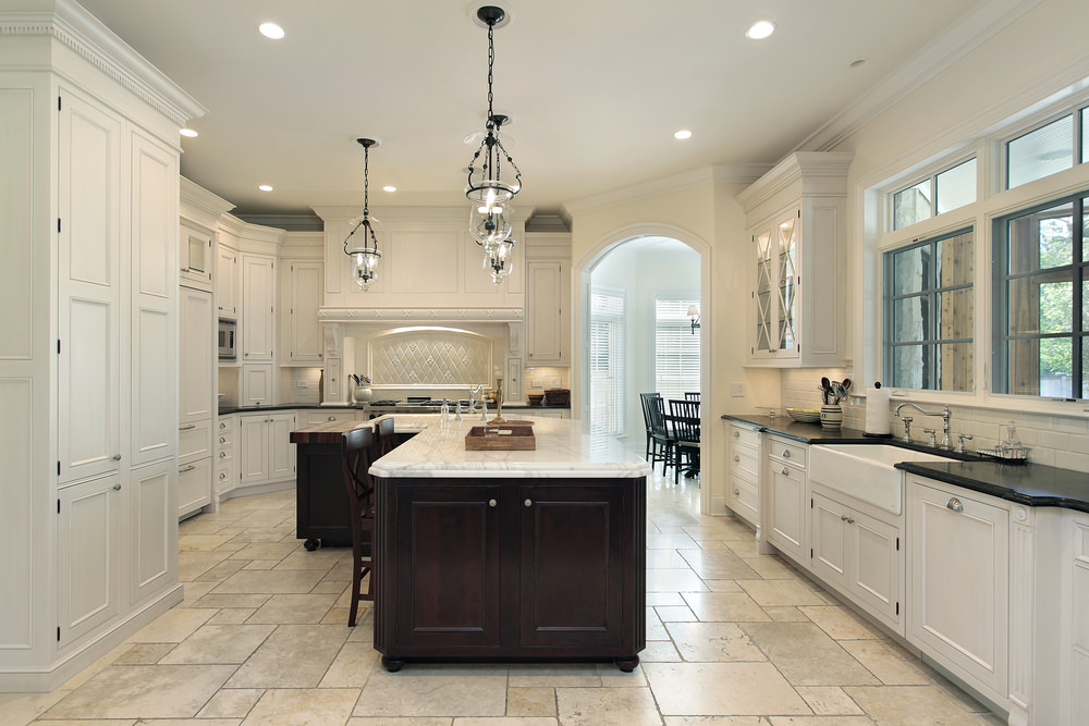 This kitchen features stylish tiles flooring, white cabinetry and kitchen counters, along with an L-shape center island.
