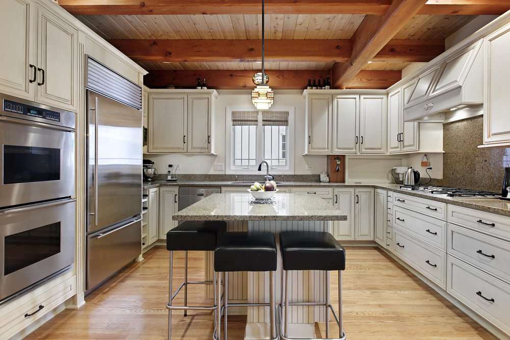 This kitchen boasts a ceiling with exposed beams lighted by a stylish pendant lighting. There's a medium-sized center island with a white granite countertop set on the hardwood flooring.