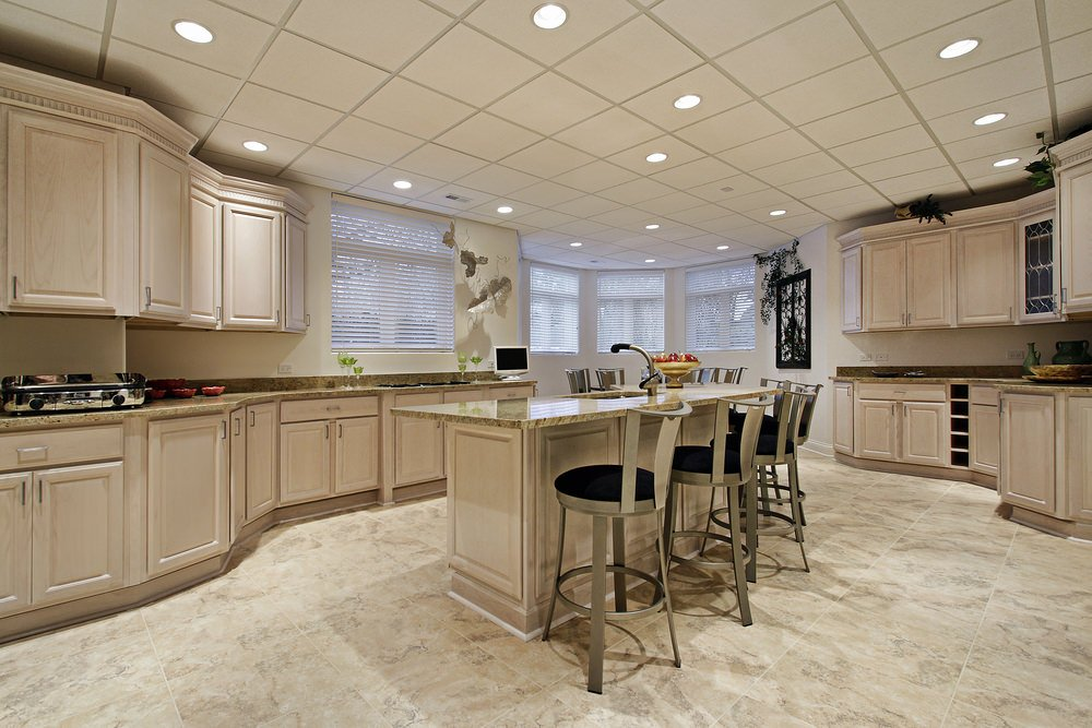 A classy kitchen featuring walnut cabinetry, kitchen counters and center island along with beautiful tiles floors.
