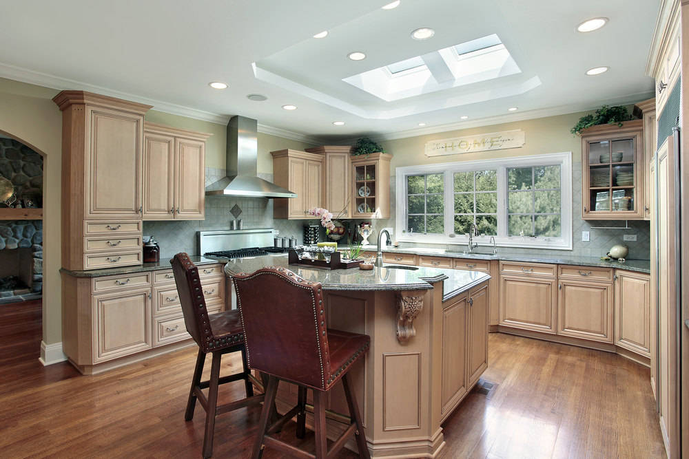 This kitchen features beige cabinetry and counters together with black granite countertops. The tray ceiling also boasts a skylight.