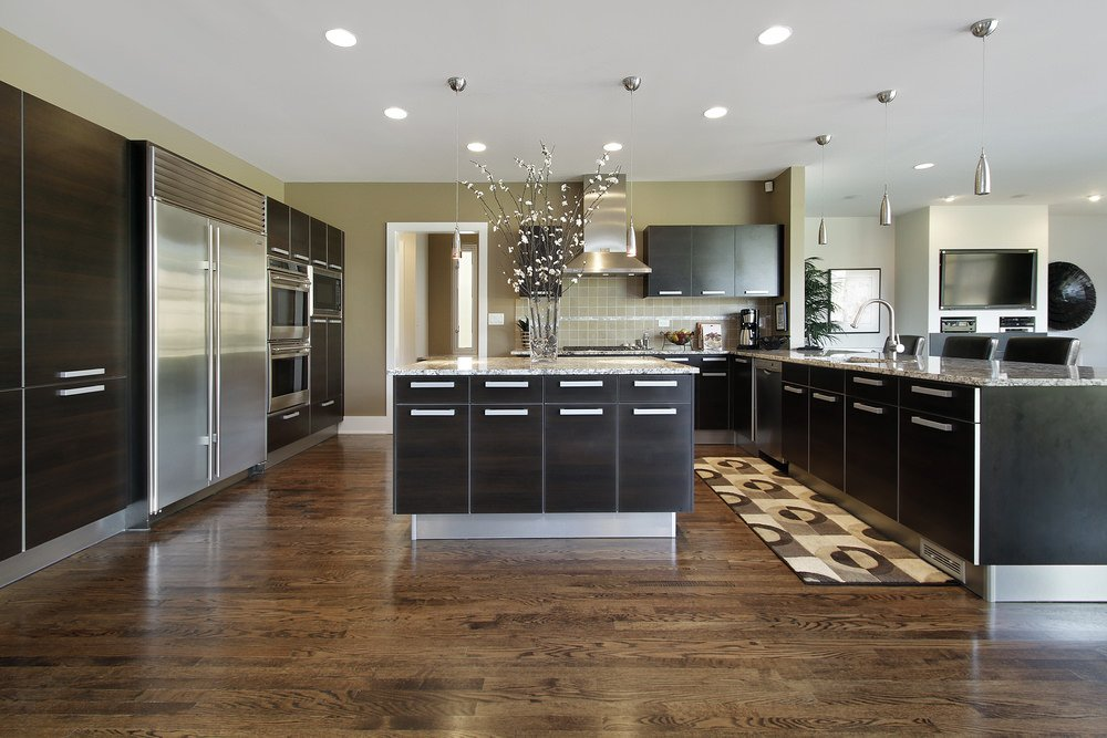 Spacious kitchen with black cabinetry and kitchen counters. It has hardwood flooring and gray walls, along with a regular ceiling with recessed and pendant lights.
