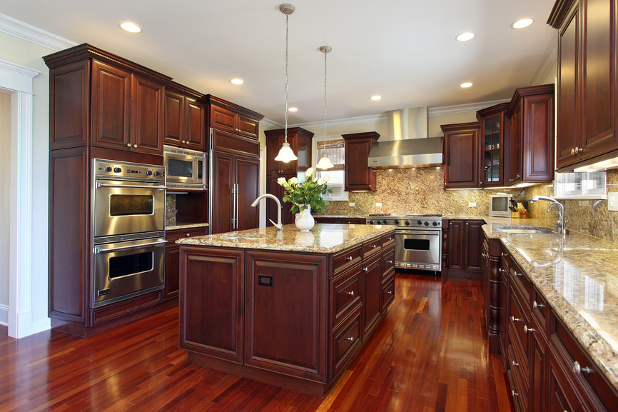 Elegant kitchen features beautiful cherry wood cabinets complemented by polished marble countertops, wooden breakfast islands lighted by small pendants and stainless steel range hood fixed to cream painted wall.