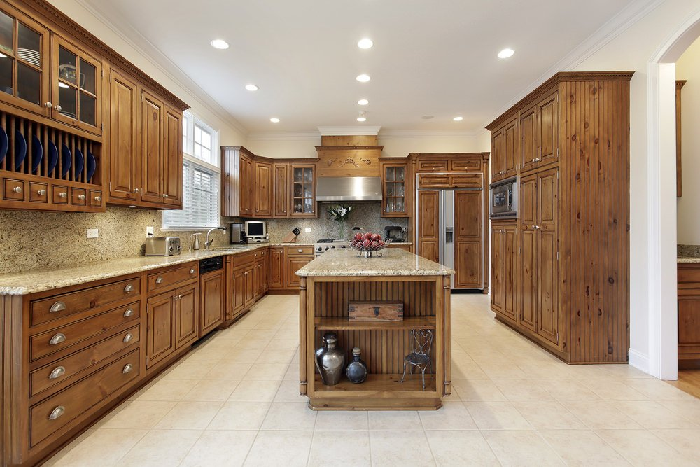 This kitchen features rustic cabinetry and kitchen counters with granite countertops. The area is lighted by recessed ceiling lights.