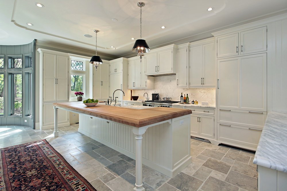 Bright and airy kitchen with white ceiling, white cabinetry, white backsplash, and a pair of pendant lighting shining on the white base cabinet island with wood surface standing near an area rug on gray tile flooring.