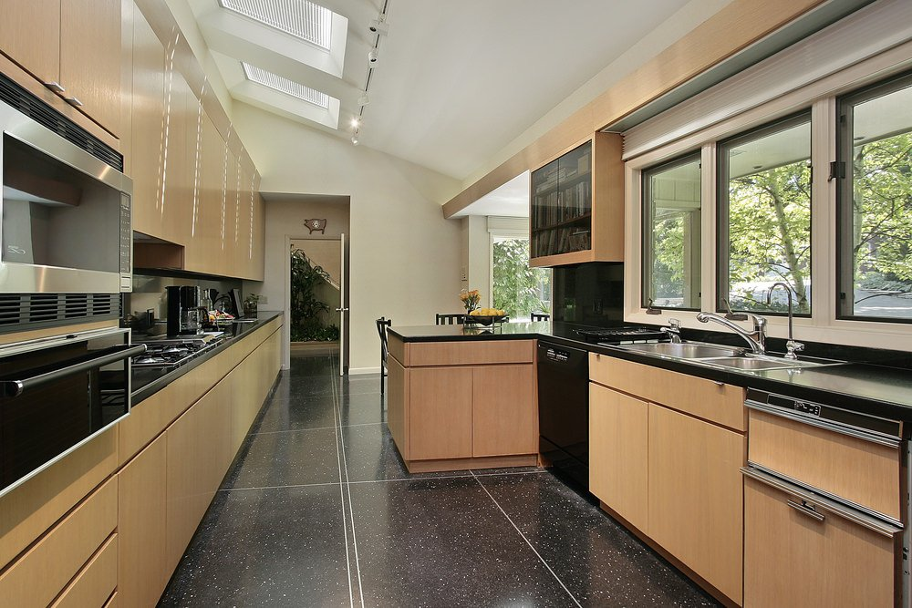 This kitchen offers stylish black flooring and kitchen counters, along with a shed ceiling lighted by track lights.