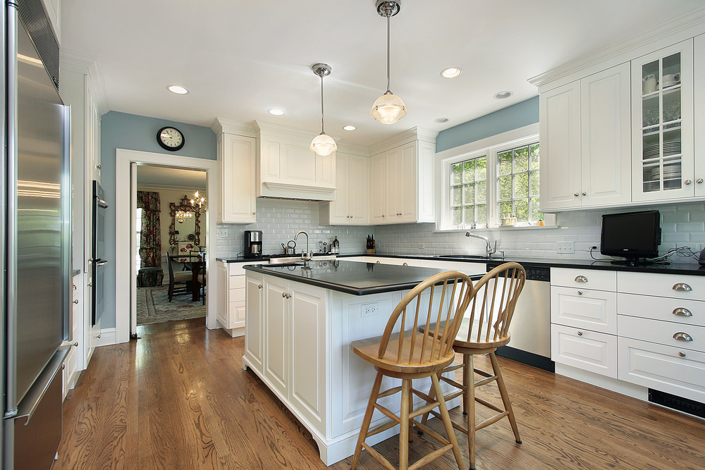 Black granite countertops accent elegant white kitchen cabinets with chrome knobs and white brick backsplash tiles. The light blue wall adds a cool ambiance to the kitchen.