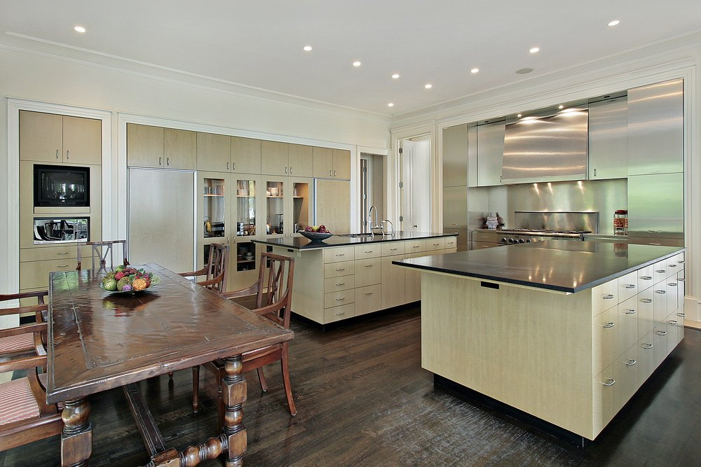 Dual light wood kitchen islands with black countertop and built-in cabinets sit on hardwood flooring. Stainless steel cabinets with range hood contrast the wood elements.