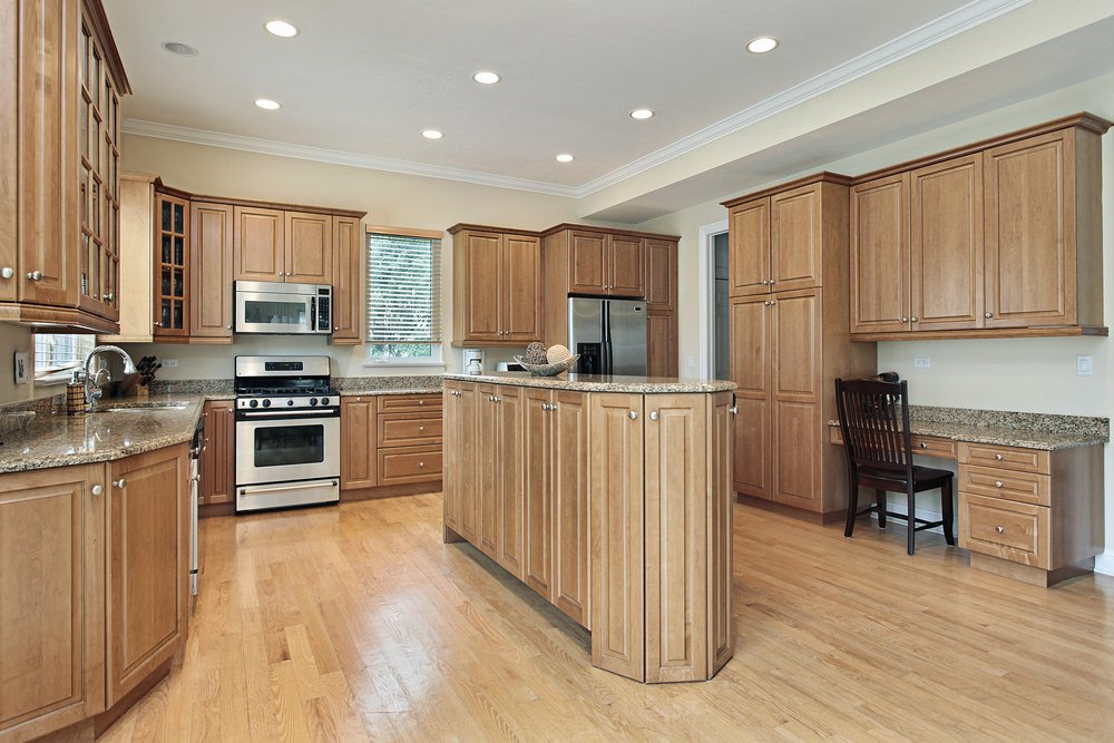 Brown kitchen with matching cabinetry and kitchen counters. It has a desk and a center island, as well as hardwood flooring.