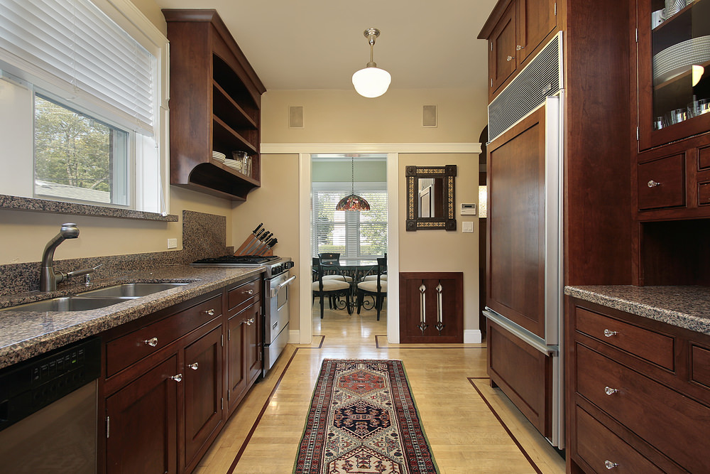 This galley kitchen with granite countertops also boasts classy flooring and lighting.