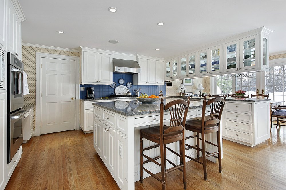 A blue-tiled backsplash with stainless steel range hood mounted on it adds some personality on this white kitchen.
