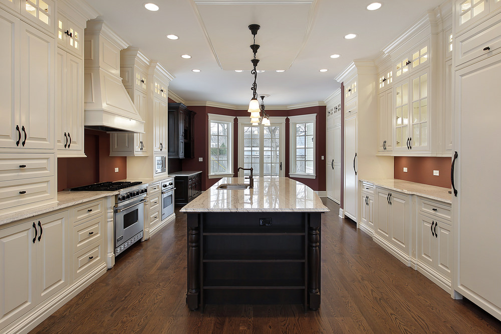 An elegant kitchen with a dark wooden breakfast island sits at the center over a hardwood flooring. It is lighted by small vintage pendants and surrounded by white cabinets on brown painted walls.