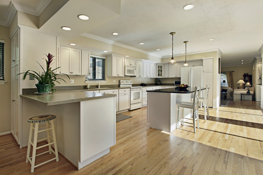 Sophisticated kitchen features white cabinets with gray marble countertop, cream painted walls, recessed lighting and a pair of pendant lights that illuminate a white center kitchen island topped with black granite over a hardwood flooring.