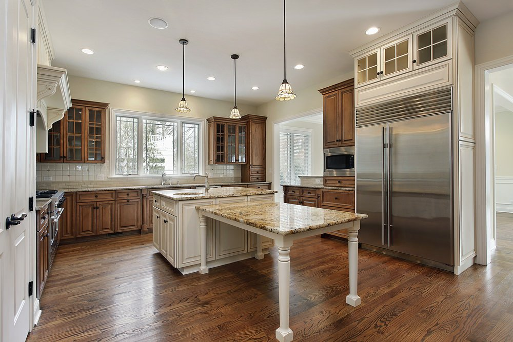 A spacious kitchen features a marble-topped table running perpendicular to the matching kitchen island. Charming pendant lights illuminate the area with the help of recessed lighting.