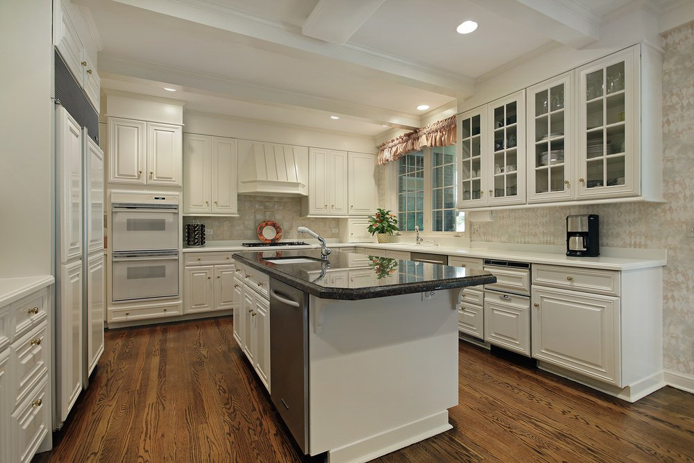 Large U-shaped kitchen with white cabinetry and counters along with hardwood flooring and recessed lighting.