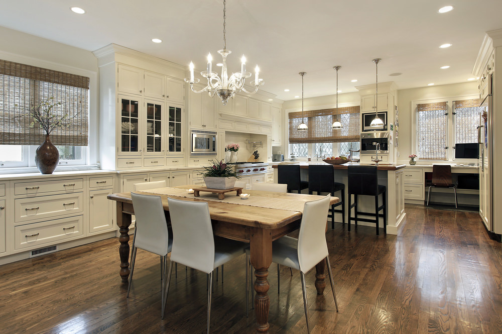 Classic glass pendants light a wooden kitchen island topped with marble countertop and lined with black cushioned chairs. The area is covered with recessed ceiling lights and surrounded with white wooden cabinets. A lovely chandelier hung over a dining space.