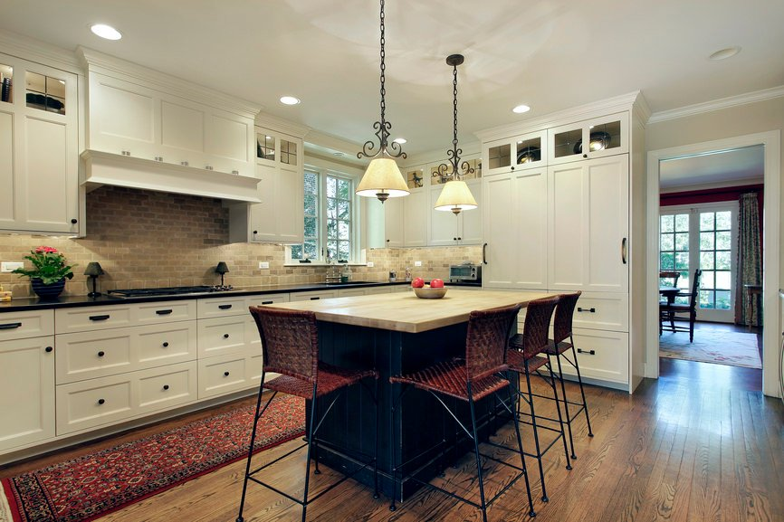 A pair of fancy pendant light shades hung over a dark wooden breakfast island where rattan counter stools sit alongside a traditional red runner on this classic white kitchen.
