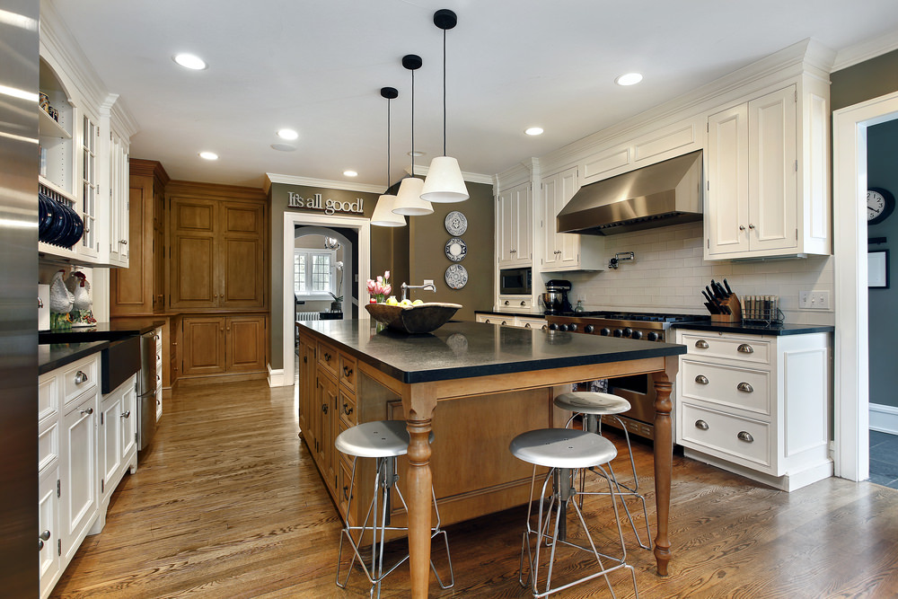 This white and black kitchen features wooden breakfast island with gray metal counter stools, white classic pendant lights and a stainless steel range hood fixed to white brick backsplash tiles.