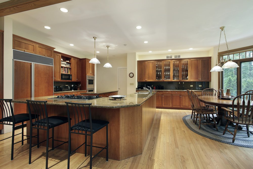 Classic kitchen surrounded with wooden breakfast island topped with marble countertop and lined with three black chairs. Space is shared by the dining area and both lighted with fancy pendant lamps and recessed lighting.