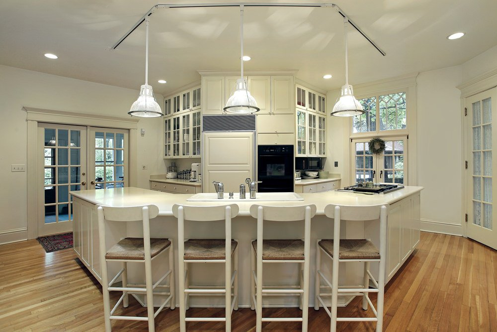 An all-white kitchen with three glass pendant lights hung over a U-shaped breakfast island, lined with four wooden chairs with cushions over a hardwood flooring.