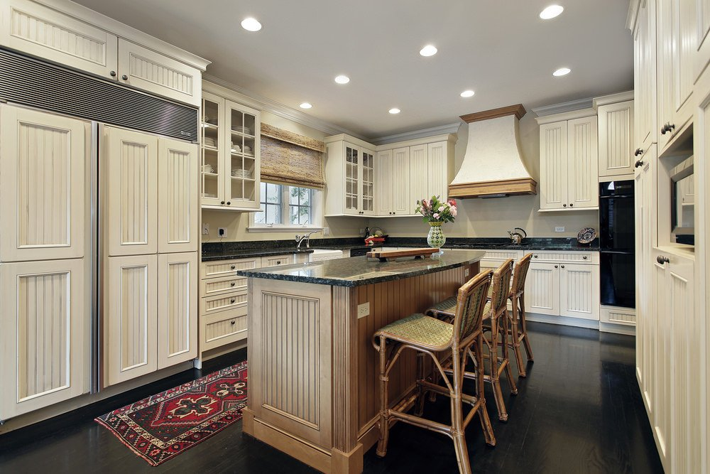 U-shaped kitchen featuring black hardwood floors matching the black granite countertops on both kitchen counters and center island.
