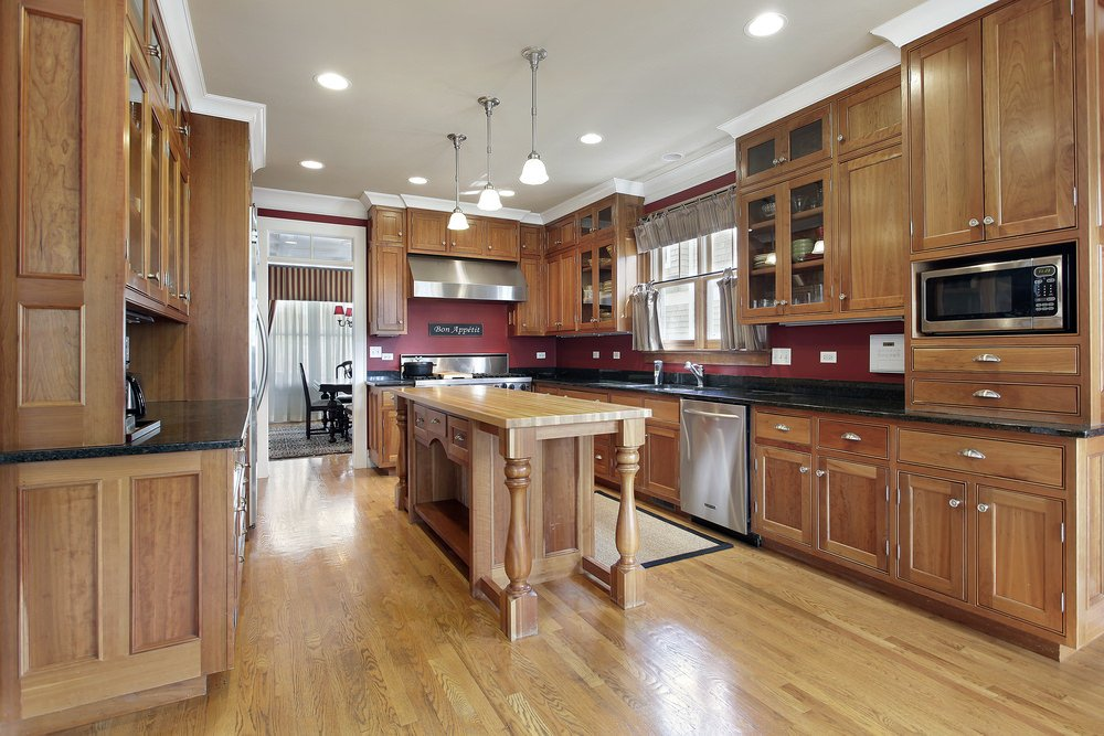 U-shaped country style kitchen with hardwood floors, central kitchen island, wooden cabinets, stainless steel appliances, recessed ceiling lights and a row of three pendant lights.