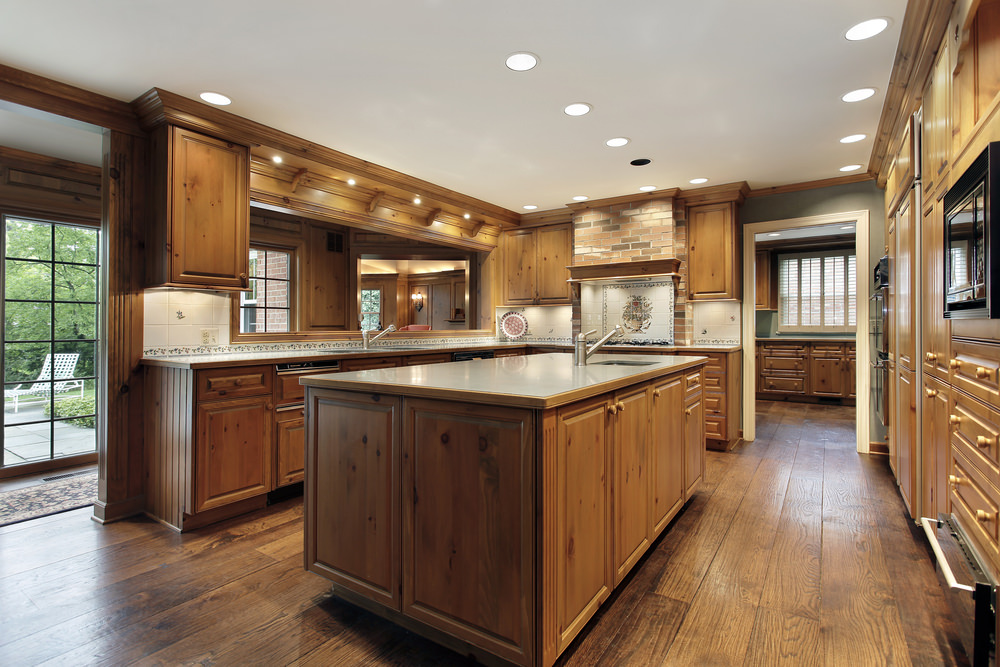 This kitchen boasts a brown center island that matches the cabinetry and kitchen counters, along with the hardwood flooring.