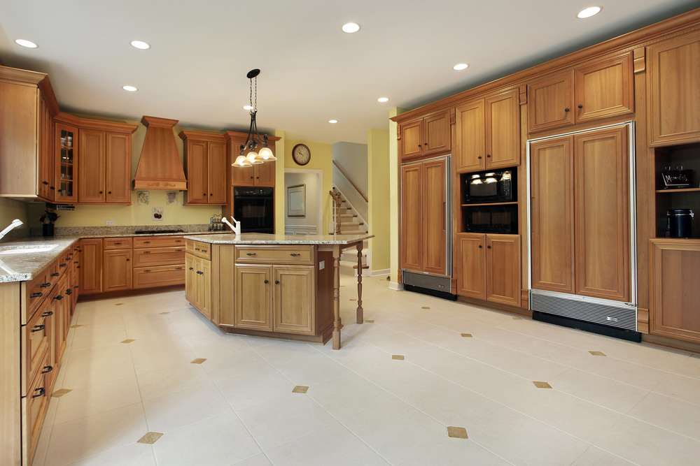 Large kitchen area featuring brown cabinetry and kitchen counters. The kitchen boasts classy tiles floors and yellow walls.