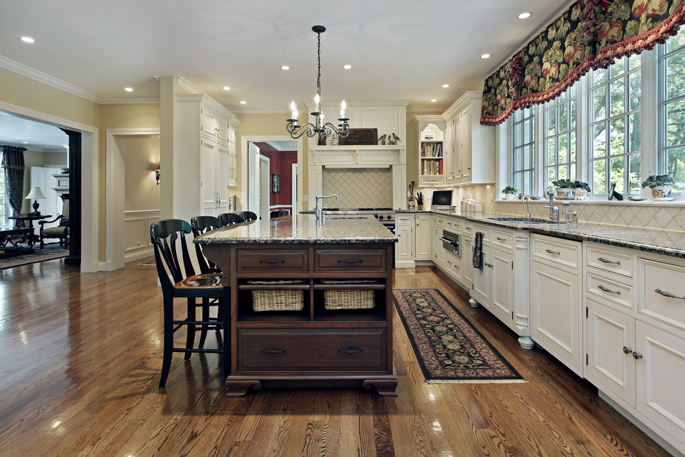 Expansive kitchen with soft yellow walls and glass windows dressed in lovely floral valence complementing the kitchen rug that lays on the hardwood flooring.