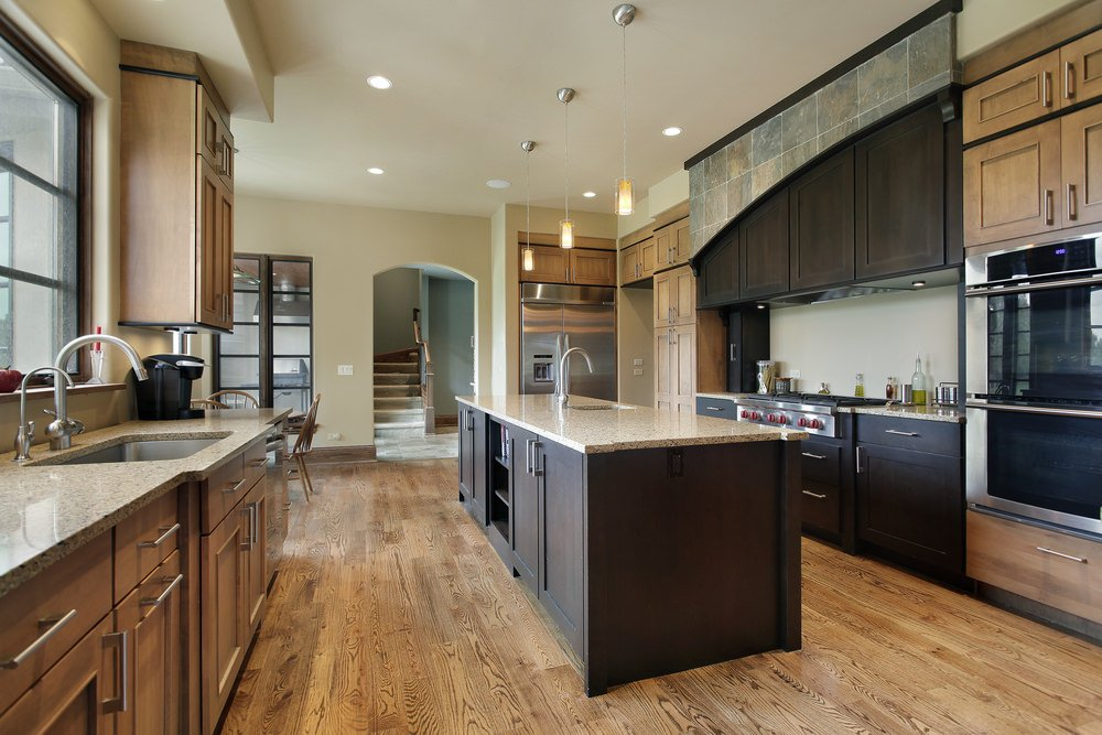 Roomy kitchen with rustic wooden cabinets on one side, and dark grayish cabinets on the other creating a stark contrast. It's well complemented by its hardwood floors and simple and small pendant lights.