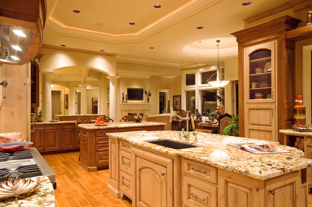 Spacious cottage kitchen with two islands, rustic cabinets, hardwood floors, coffered ceiling, and marble countertops.