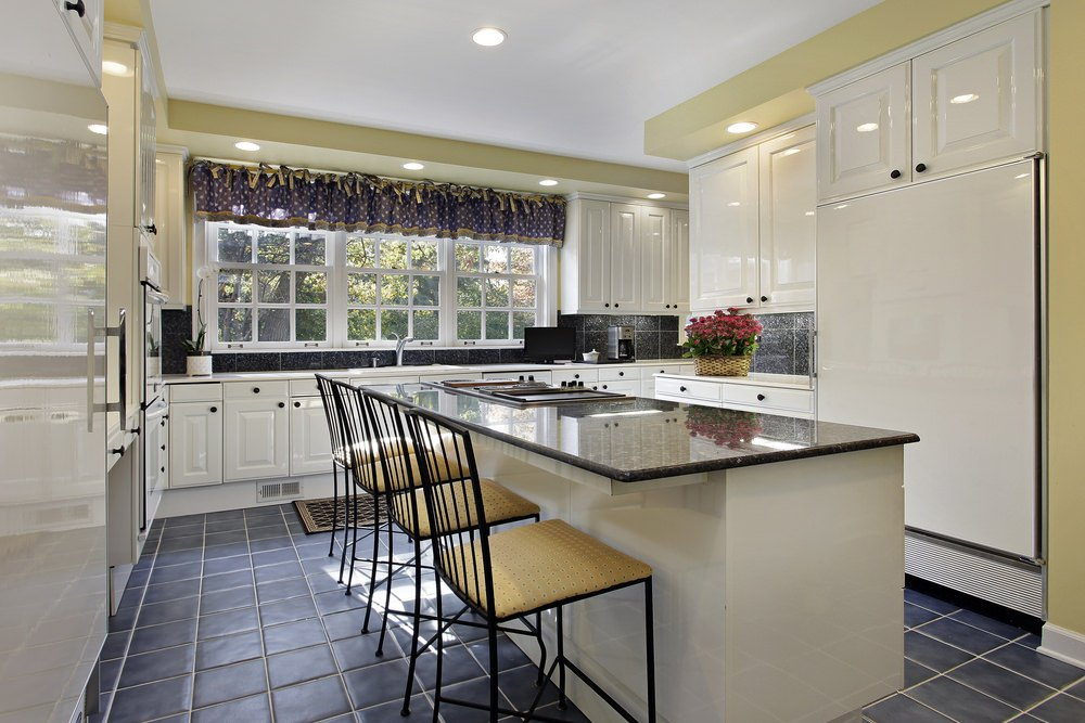 Large U-shaped kitchen with a massive center island equipped with a dark-finished countertop. The tiles flooring looks stylish.