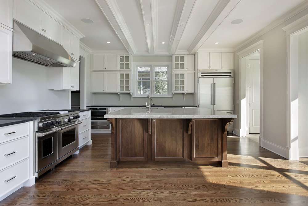 This kitchen features a center island matching the hardwood flooring and has a marble countertop. The kitchen counters feature black countertops.