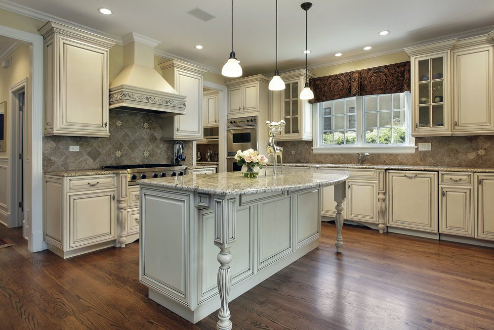 A kitchen featuring hardwood floors, white cabinetry and kitchen counters, along with a stylish center island with space for a breakfast bar.