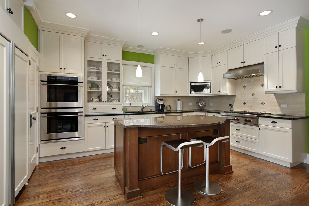Large U-shaped kitchen with a hardwood flooring and a small center island with granite countertop lighted by pendants and recessed lights.