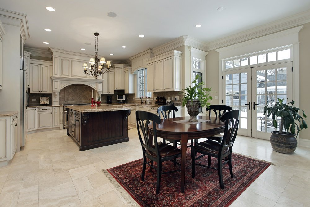 Large U-shaped kitchen with a glamorous chandelier lighting up the area. The large center island offers a marble countertop.