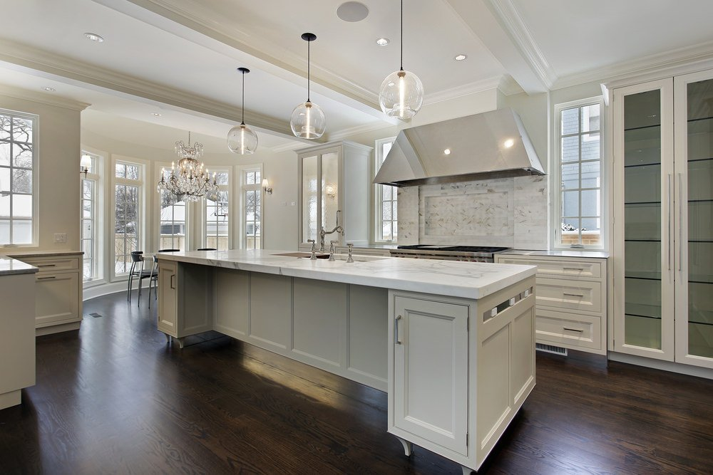 This large kitchen offers a large center island with lovely white marble countertop lighted by elegant pendant lights set on the tray ceiling.