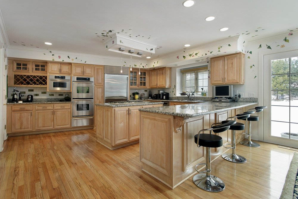 Large kitchen with hardwood flooring and walnut cabinetry. White walls and decorated ceiling look gorgeous with each other. The peninsula matches the small center island well.