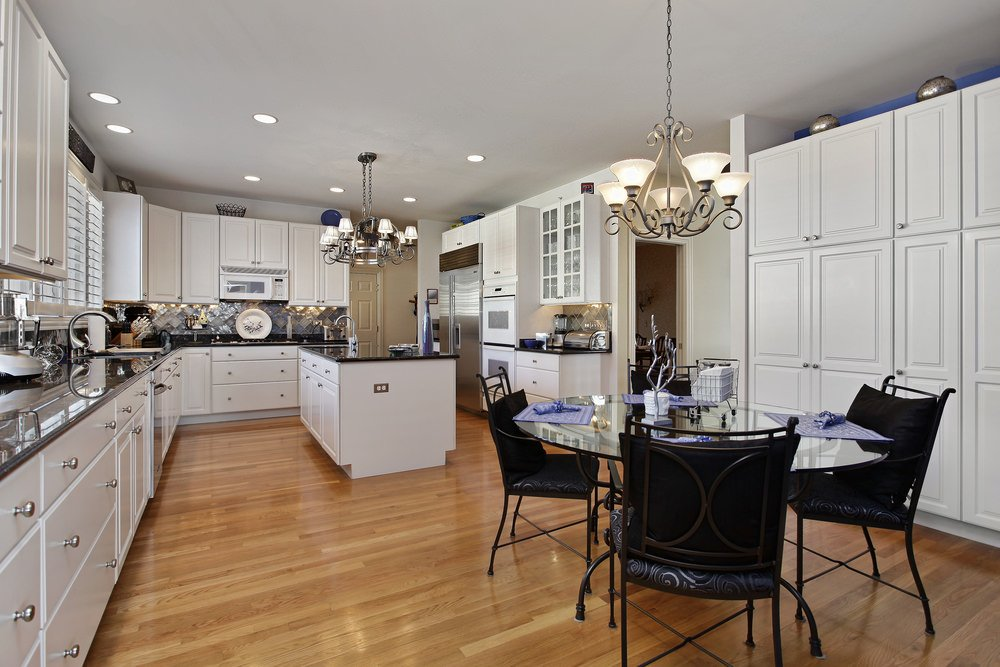 Spacious eat-in kitchen with a round glass top dining table and black metal chairs surrounded by white cabinetry that's fitted with chrome knobs.
