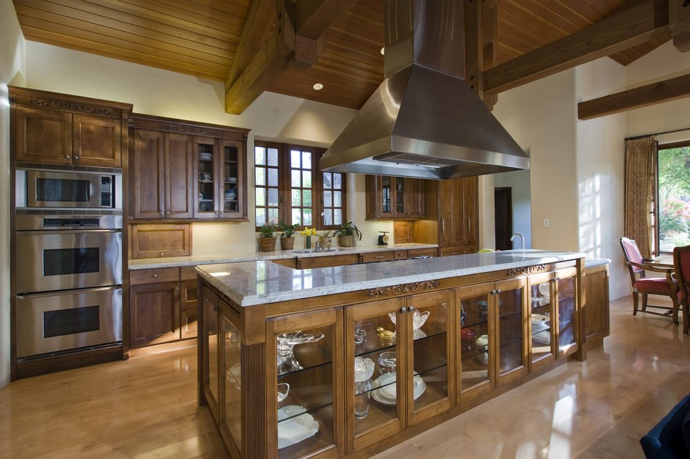 Large kitchen with a massive center island featuring a marble countertop. The hardwood flooring matches well with the wooden ceiling with exposed beams.
