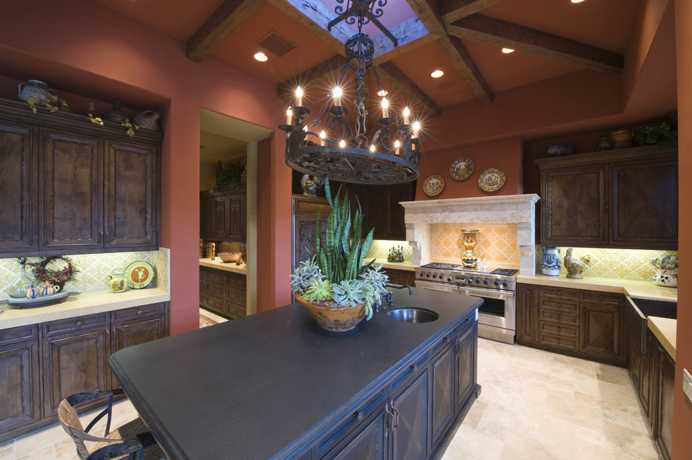 This kitchen looks so elegant with its black center island and rustic cabinetry and counters lighted by a glamorous chandelier set on the ceiling with beams.