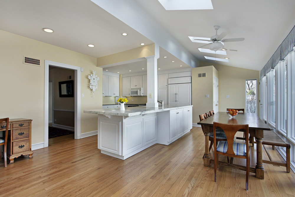 A dine-in kitchen offers glass windows and skylights fixed to the vaulted ceiling. It has white cabinetry that blends well with the soft yellow walls contrasted by a dark wooden dining set.