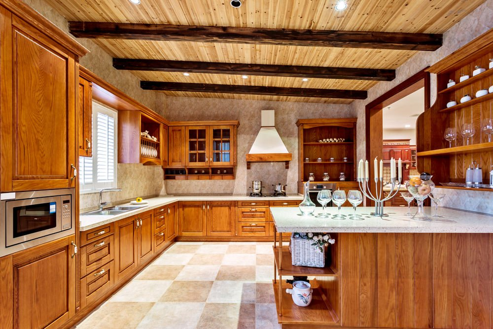 Large kitchen with beautiful counters with white granite countertops. The tiles flooring looks classy while the ceiling with beams is just stunning.