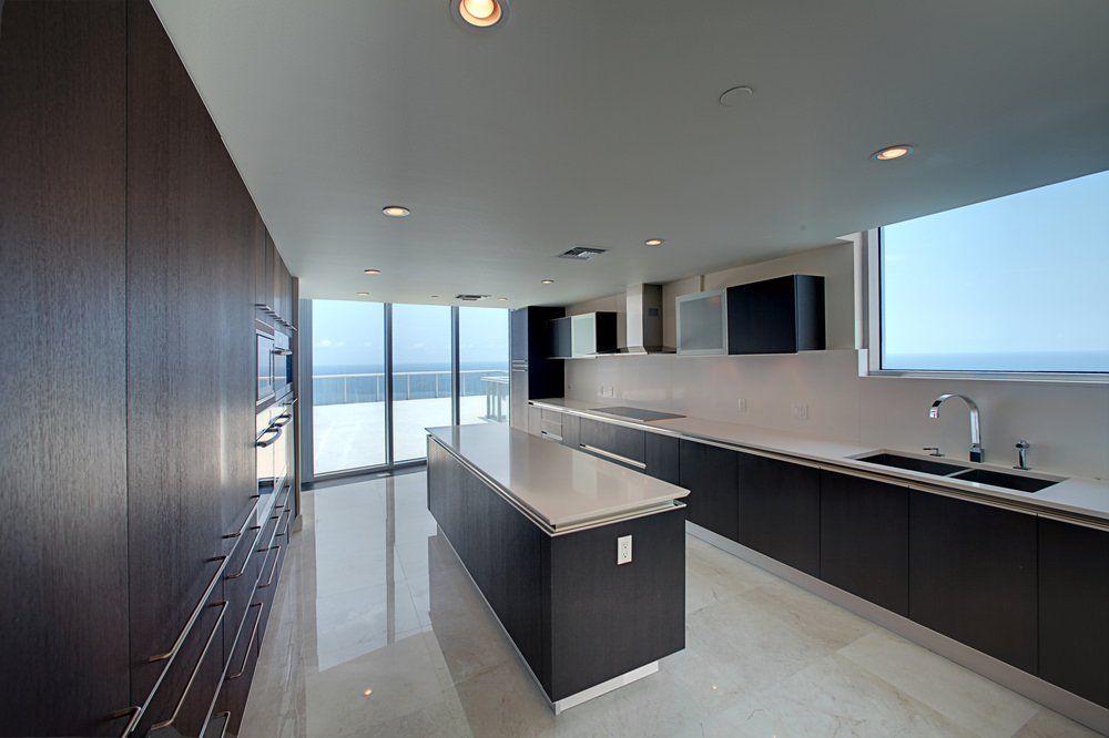 Modern kitchen setup with dark hardwood shade. The smooth counters matches the sparkling tiles flooring. The narrow center island provides additional space for preparing meals.