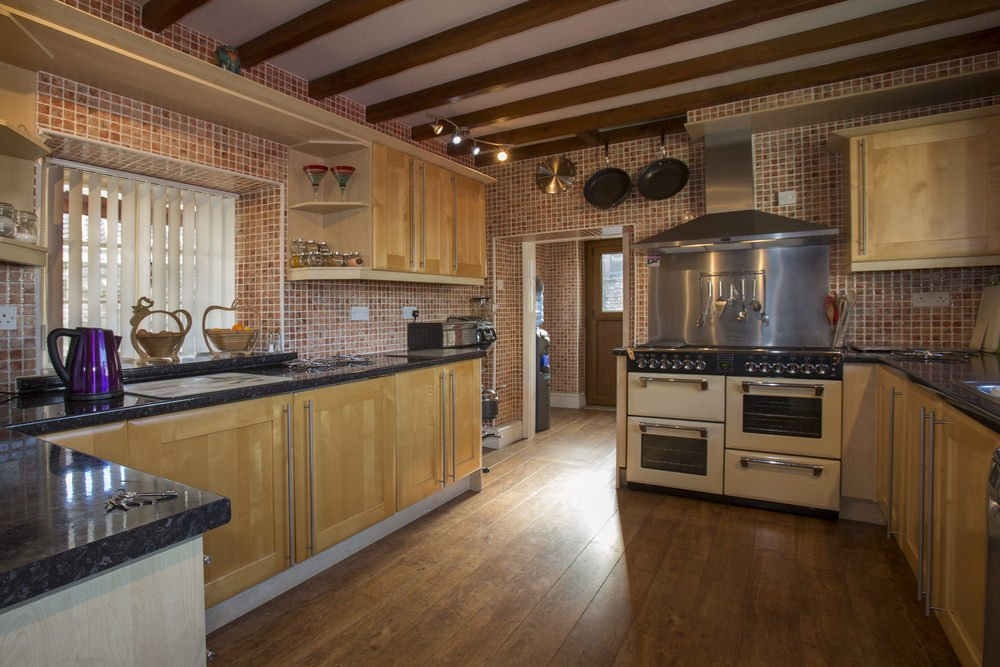 This kitchen features tiles walls and hardwood flooring, along with a ceiling with beams.